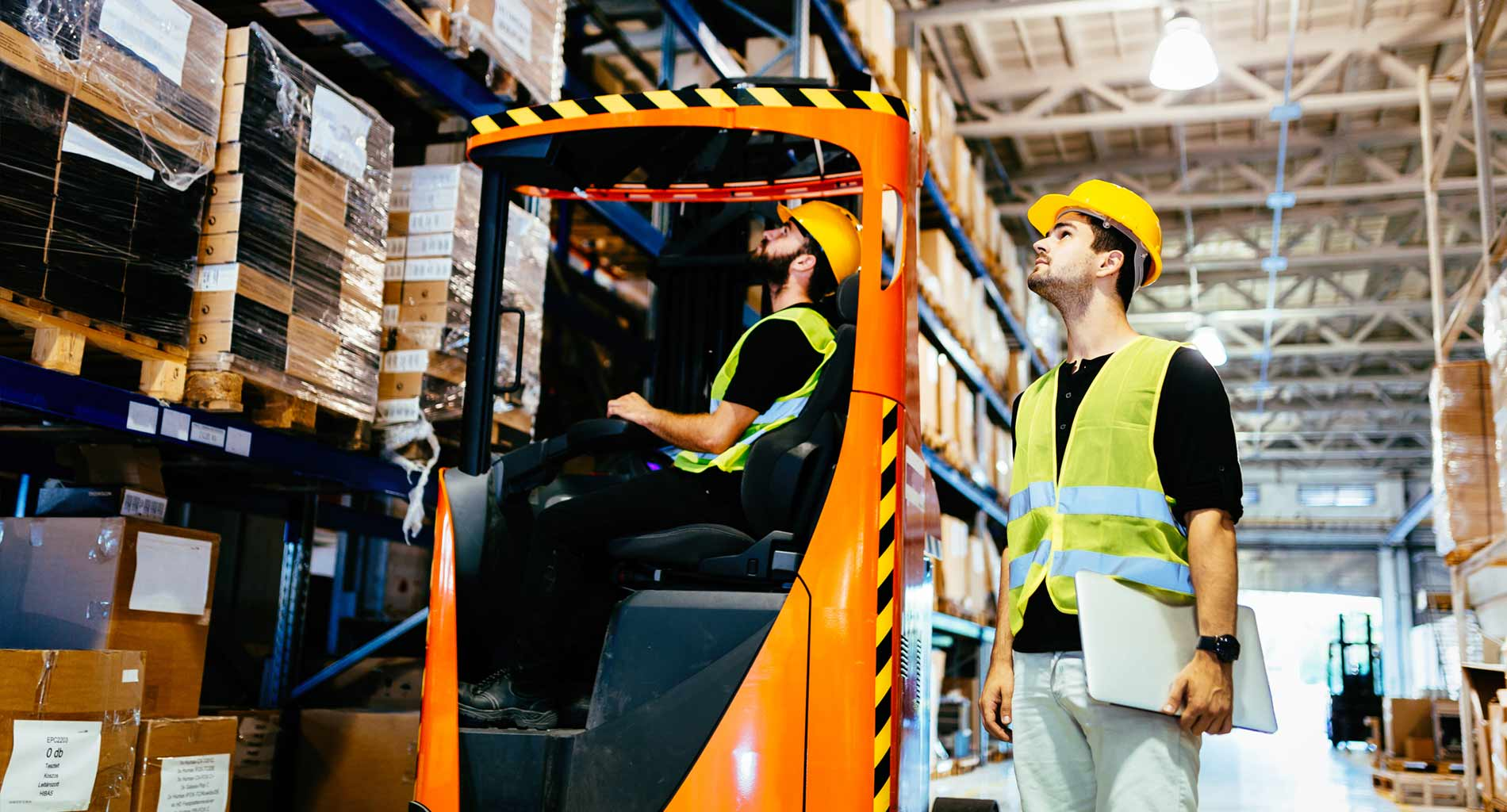 Forklift truck and driver in warehouse.